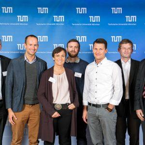 Die Magazino-Gründer Frederik Brantner (2.v.l.), Nikolas Engelhard (4.v.l.) und Lukas Zanger (3.v.r.) mit der Jury des Presidential Entrepreneurship Awards.